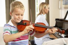 Young boy playing violin accompanied by teacher Stock Photos