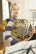 Girl holding French horn at home Stock Photos