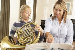 Girl playing French horn in music lesson Stock Photos