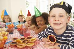 Young children eating jam tarts at birthday party Stock Photos