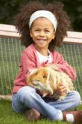 Young girl in garden holding guinea pig Stock Photos