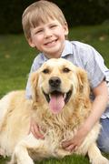Young boy in garden with golden retriever Stock Photos