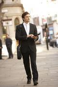 Businessman with tablet walking down street Kuvituskuvat