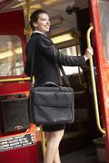 Businesswoman standing on Routemaster bus platform Stock Photos