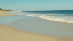 Looking Down A Sandy Beach As Waves Wash Ashore Stock Footage