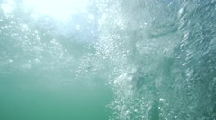 Bubbles under the water rise up towards the surface illuminated by sunlight Stock Footage