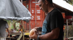 A Man peels a Coconut on the Island of PALAU Stock Footage
