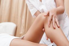 Masseuse works with feet and legs - stock photo