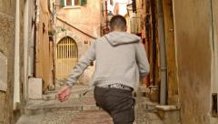 Young Man walks in the Old Neighborhood in FRANCE Stock Footage