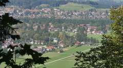 Gently blowing leaves frame a view of Hohenschwangau village - 4K Stock Footage