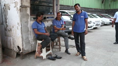 Four Indian men posing at auto mechanics garage. Stock Footage