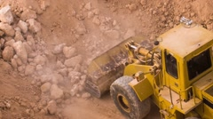 Top view excavator loading crushed rock on dumper truck Stock Footage