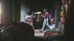 Man passing by the dark passage full of sorted sacks with laundry in Mumbai. Stock Footage