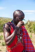 MASAI MARA,KENYA, AFRICA- FEB 12 Masai shaman is drinking a cup of cow blood in - stock photo