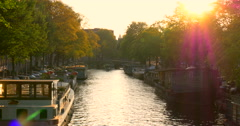 Amsterdam canal canals sunset Netherlands Holland sun rays set sunrays beams red Stock Footage