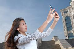 Young japanese women with long hair do selfie in city park against steps clear Stock Photos