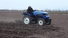 Stock Video Footage of Cultivation of fields on compact tractors. Agricultural machinery on the spring