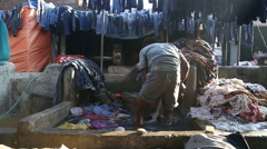 Indian man taking clothes out of a washing pool in Mumbai. Stock Footage