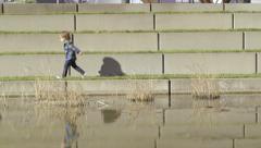 Little Boy Enjoys Running Alongside Pond In A City Park Stock Footage