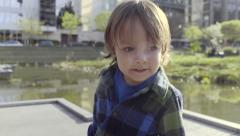 Excited Little Boy Searches For Fish At A City Park Pond (4K) Stock Footage