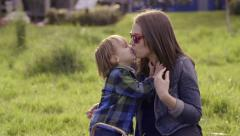 Little Boy Gives His Mother Kisses In The Park Stock Footage