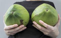 Woman breast coconut fruit implant upsize metaphor concept Stock Photos