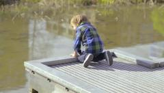 Little Boy Looks Over The Edge Of A Dock, Looking For Fish Stock Footage