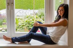 woman sitting on window - stock photo