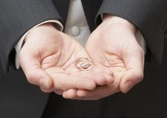 Close Up Of Groom Holding Wedding Rings - stock photo