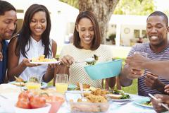 Group Of Friends Enjoying Outdoor Meal At Home - stock photo