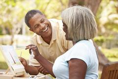 Senior Couple Sitting At Outdoor Table Painting Landscape - stock photo