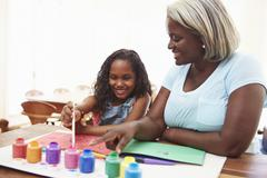Grandmother Painting Picture With Granddaughter At Home Stock Photos