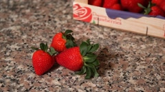 Strawberries on granite table with wooden box in the background Stock Footage