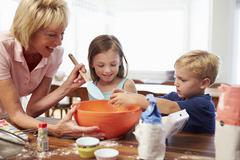 Grandmother And Grandchildren Baking Together At Home Stock Photos