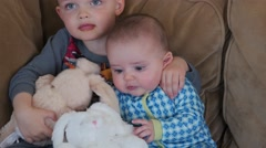 A boy and baby on couch with bunny's easter morning Stock Footage