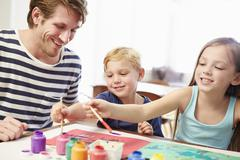 Father Painting Picture With Children At Home Stock Photos
