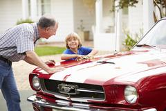 Grandfather And Grandson Cleaning Restored Classic Car Stock Photos