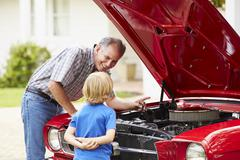 Grandfather And Grandson Working On Restored Classic Car Stock Photos