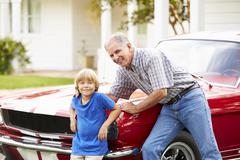 Portrait Of Grandfather And Grandson With Restored Car Stock Photos