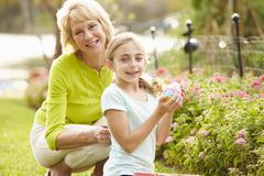 Grandmother With Granddaughter On Easter Egg Hunt In Garden Stock Photos