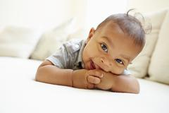 Smiling Baby Boy Lying On Tummy At Home Stock Photos