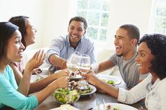 Group Of Friends Enjoying Meal At Home Together Stock Photos