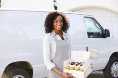 Female Baker Delivering Cakes Standing In Front Of Van - stock photo