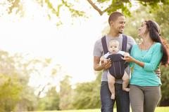 Family With Baby Son In Carrier Walking Through Park - stock photo