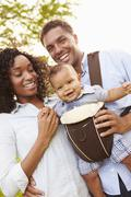 Family With Baby Son In Carrier Walking Through Park Stock Photos