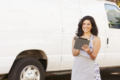 Woman Wearing Apron With Digital Tablet In Front Of Van Stock Photos