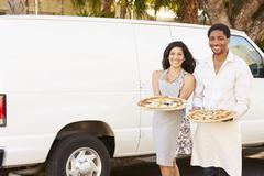 Couple Delivering Pizza Standing In Front Of Van - stock photo