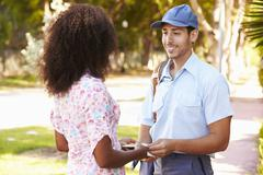 Mailman Delivering Letters To Woman - stock photo