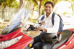 Young Man Riding Motor Scooter To Work Stock Photos