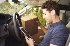 Delivery Driver Sitting In Van Using Digital Tablet - stock photo